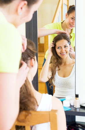 kindred: Happy young girls combing the hair in front of mirror