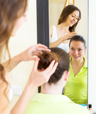 combing: Cheerful young girls combing the hair in front of mirror Stock Photo
