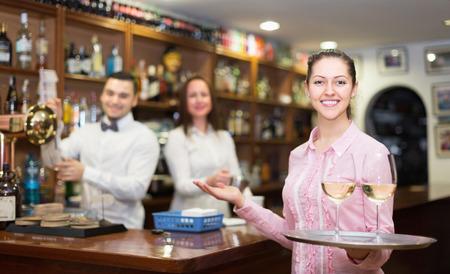 hospitality staff: Positive brunette waitress and barmen working in modern bar