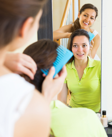 cognate: Happy young women combing the hair in front of mirror