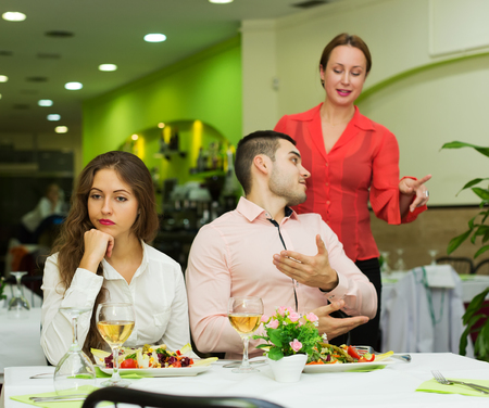 angry couple: unpleased hombre hablando con el gerente de cortes�a en el restaurante Foto de archivo