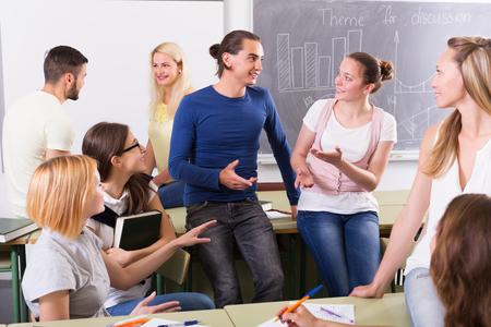 salon de clases: Varios estudiantes positivos que tienen una conversación sentado en el salón de clases