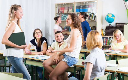 amigas conversando: Varios estudiantes sonrientes que tienen una conversaci�n sentado en el sal�n de clases