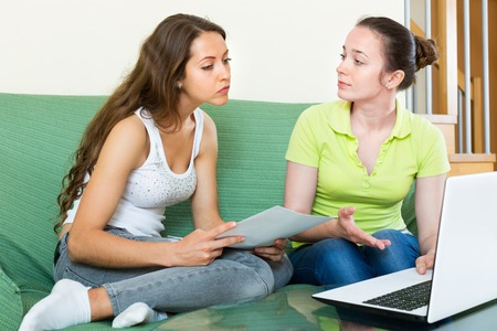 ruminate: Unhappy girl looking financial documents with laptop in home interior Stock Photo