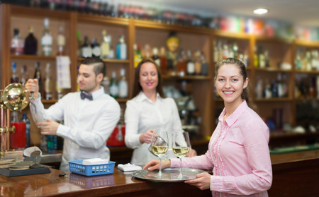 bartenders: Waitress holding tray with glasses, bartenders at the distance