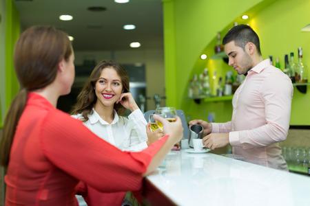 barman: TTwo female friends flirting with handsome barman