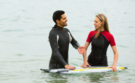 waist deep: Young active couple swimming in wetsuits with surf board Stock Photo