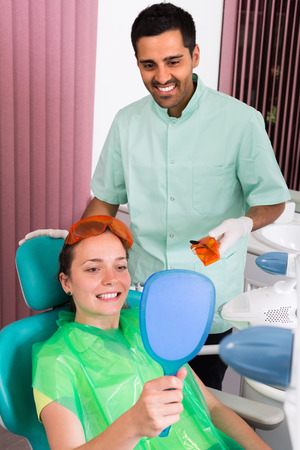 25s: Happy young female patient whitening  teeth in the dental clinic