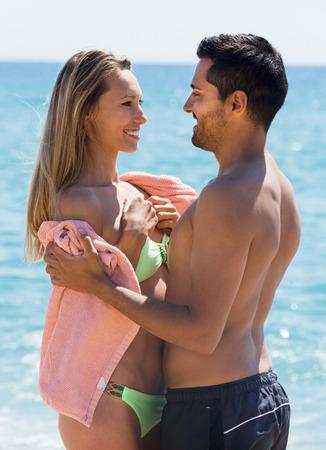 mujeres juntas: Retrato de adultos felices pareja envuelta en una toalla de pie en la playa de arena