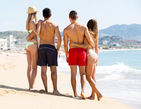 mujeres juntas: dos parejas positivos que abrazan en la playa disfrutando de romance y sol