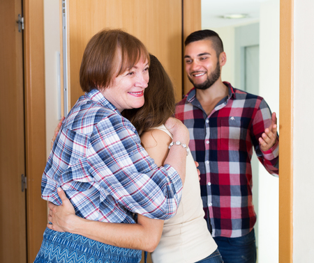 adults: Adults people greeting mother at threshold Stock Photo