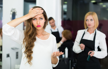 esthetics: Portrait of unhappy young girl at the hairdressing salon