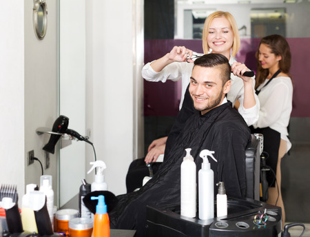 peignoir: Positive young guy cuts hair at the hair salon. Focus on the man Stock Photo