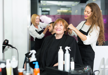 esthetics: Elderly woman at the hair salon with girl barber doing haircut  and smiling