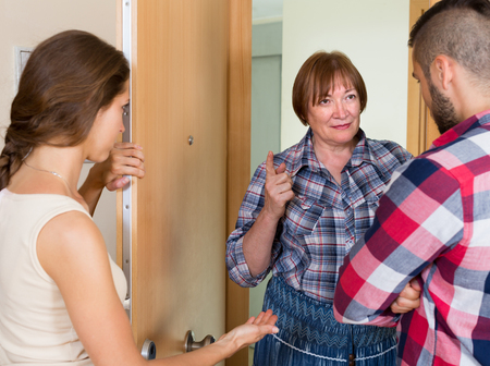 neighbour: Young family arguing with displeased elderly female neighbour in the doorway
