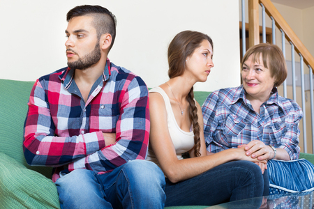 sullen: Mother comforting young sullen daughter in living room Stock Photo