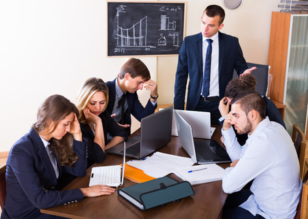 occupations and work: Manager shouting to employees at group meeting indoors