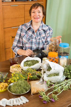 heterogeneous: Mature woman with herbs at table in home