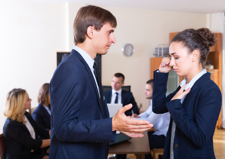 severely: Manager severely lecturing upset team member at office meeting