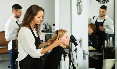 Woman hairdresser doing hairstyle for young men