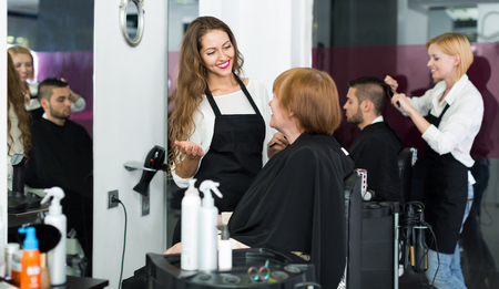 barbero: peluquero adulto americano hace el corte para la mujer madura