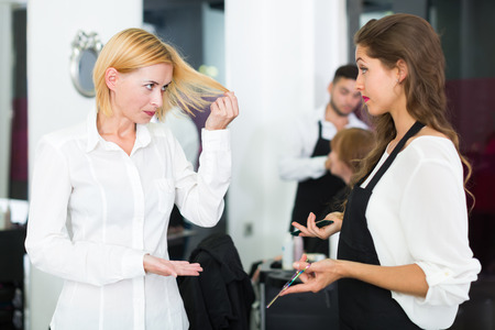 negatively: Angry young female client negatively talking with the hairdresser
