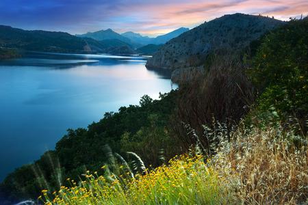 LUNA: mountains lake in summer sunrise. Barrios de Luna reservoir. Leon,  Spain