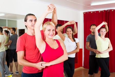 latino dance: Cheerful couples dancing Latino dance in class