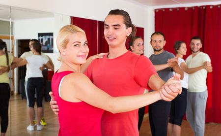 Happy smiling young adults dancing pair dance in studio