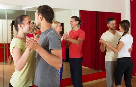 european people: Group of positive european people dancing salsa in studio