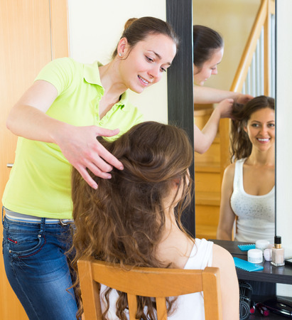 cognate: Happy smiling young woman brushing her friend in front of the mirror at home