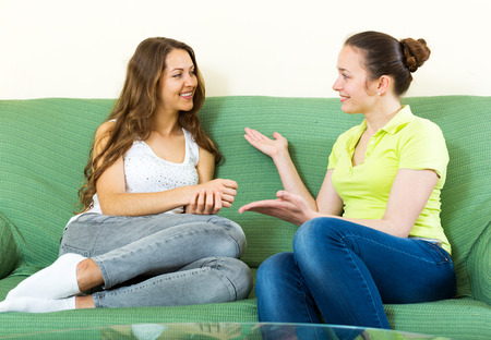 blabber: two happy woman talking on sofa in home interior