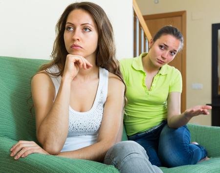 lesbienne: Deux jeunes femmes m�contents assis sur le canap� apr�s querelle � la maison Banque d'images