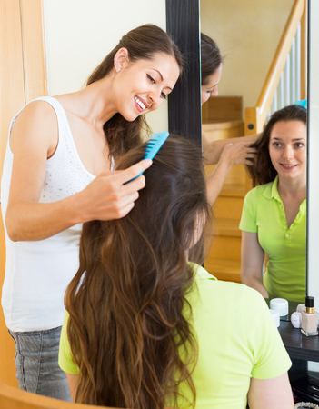 kindred: Positive beautiful girl doing hairstyle for her girlfriend Stock Photo