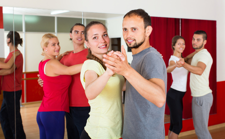 unprofessional: Smiling young couple enjoying of partner dance in class
