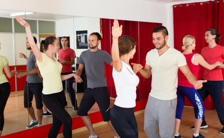 Happy men and women enjoying active dance in dance studio