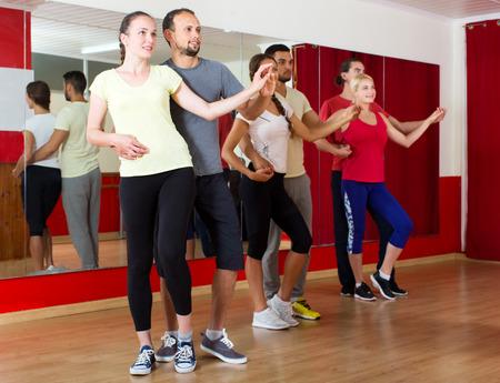 latino dance: Group of  people dancing salsa in studio