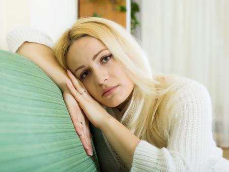 solter�a: Crying mujer rubia en el sof� Foto de archivo