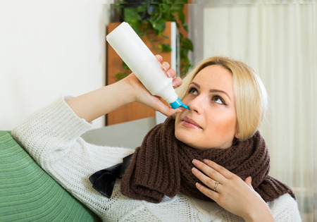 catarrh: Sick blonde girl with treatment for rhinitis at home Stock Photo