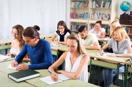diligente: Estudiantes diligentes escribiendo notas en sus cuadernos en el aula durante la lecci�n