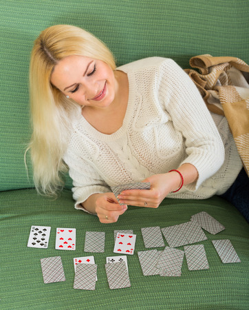 25s: Young smiling blonde woman playing solitaire at domestic interior