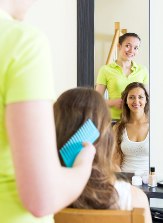cognate: Positive girls combing the hair in front of mirror