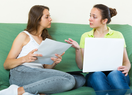 calculated: Sad women with financial documents and laptop sitting on sofa at home