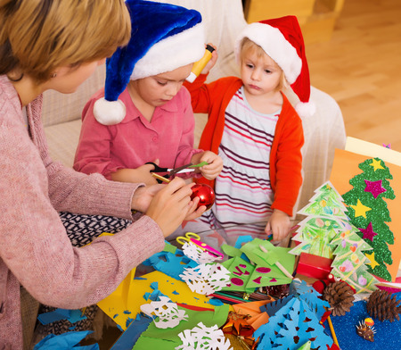 flay: Young nanny helping little daughters  to make decoration for Xmas