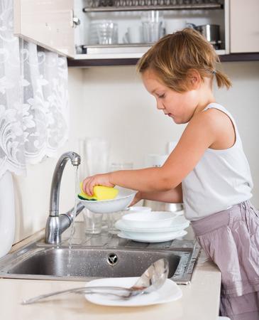manos limpias: lavar los platos pequeños niña en la cocina Foto de archivo