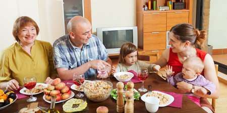 celebratory: Portrait of happy multigeneration family posing together over celebratory table at home interior