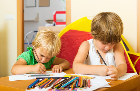 gladful: Two little children together with pencils in home interior Stock Photo
