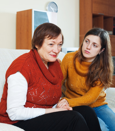 home comforts: Adult daughter  comforting sad mature woman at home