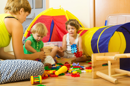 Joven madre y los niños jugando con juguetes en el hogar