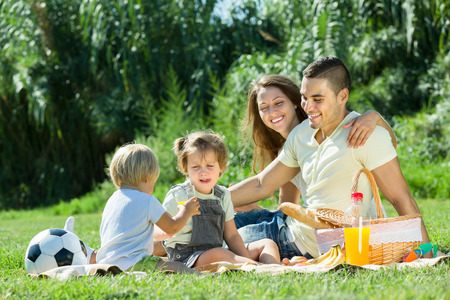 Young cheerful family with little daughters having holiday with picnic at park. Focus on man Stock Photo